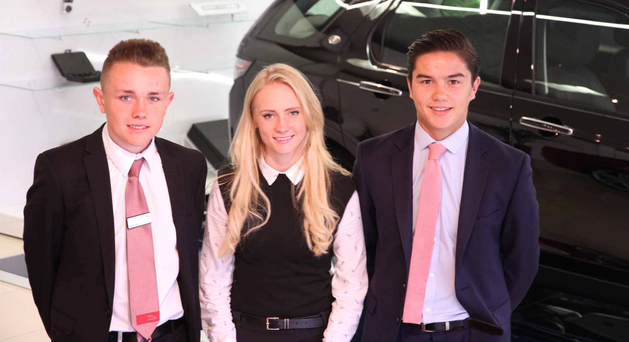 An image of three apprentices stood in front of a Range Rover